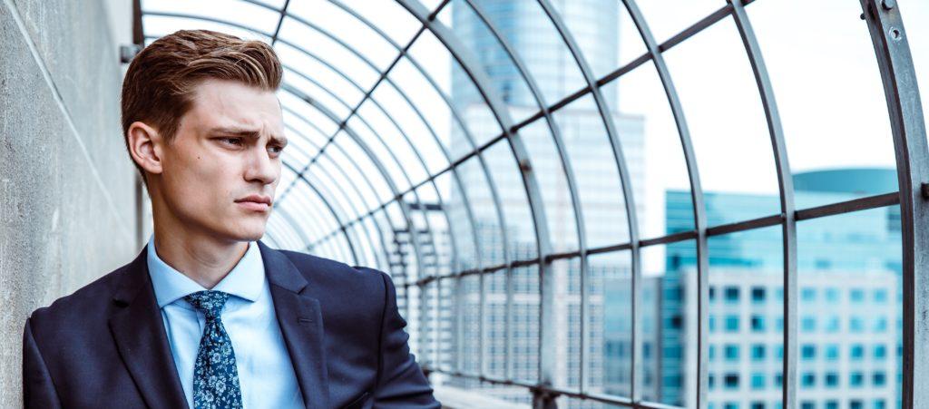 Tankefull, bekymret eller deprimert mann i dress ser ut over storbyen. Er han mindre mandig om han søker psykologhjelp?