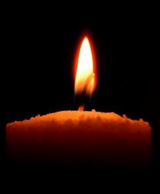 Brennende stearinlys på svart bakgrunn