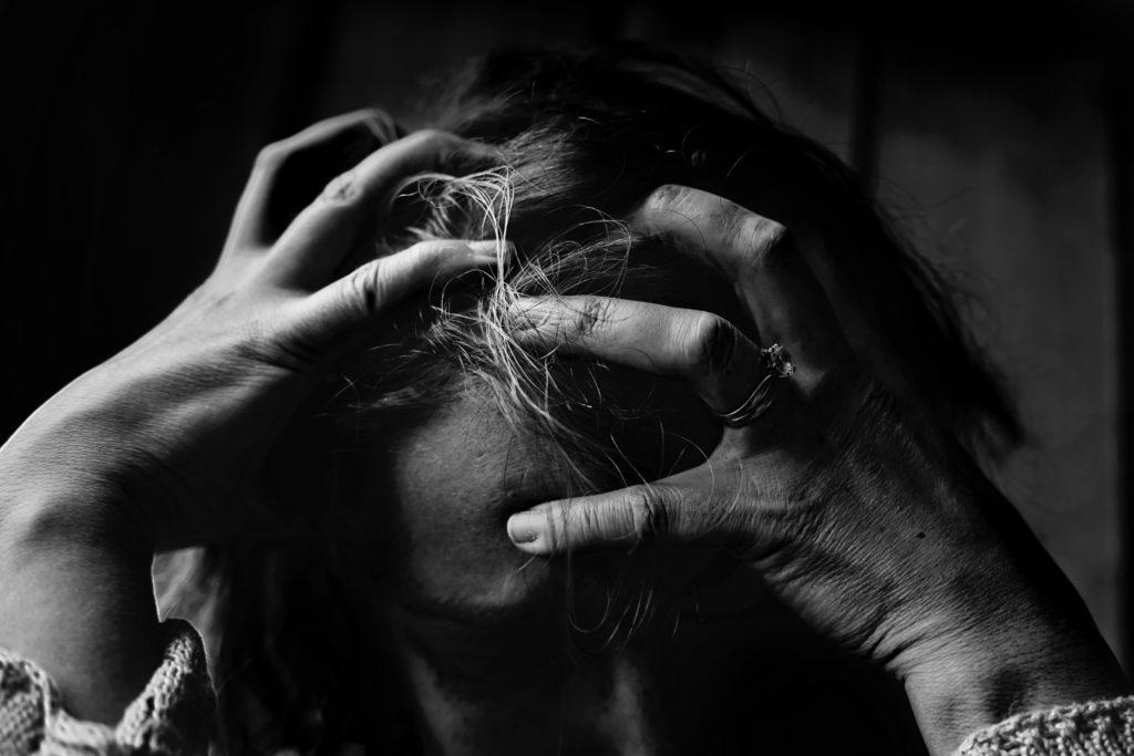Person i bekymring, som holder begge hender til hodet